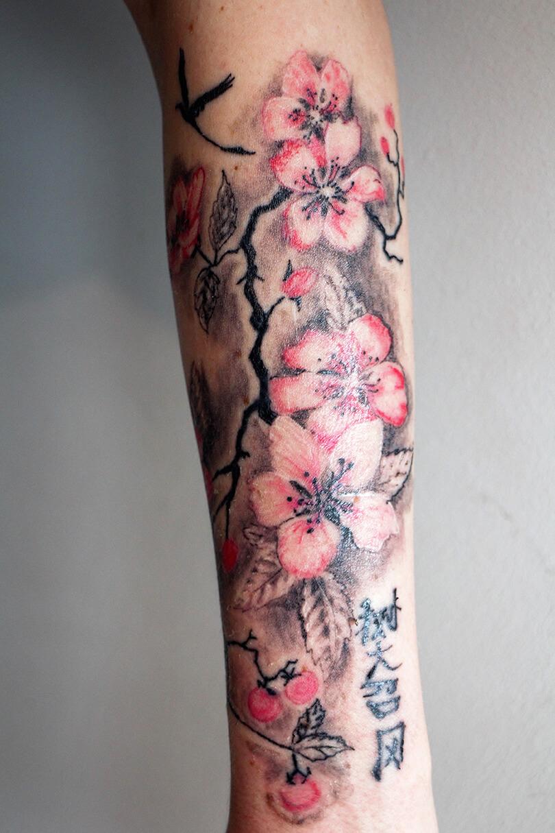 Cosmopolitan Tattoo - Avant bras femme, fleurs de cerisiers couleurs, branchages graphiques, motif inspiration japonaise