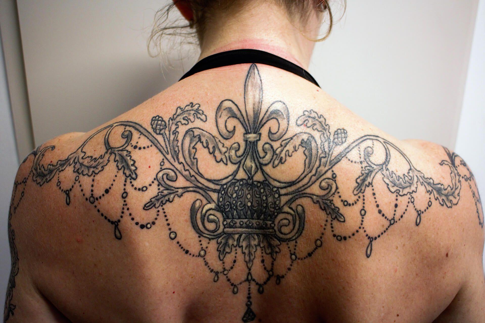 Cosmopolitan Tattoo - Création tatouage baroque, dos féminin, noir et blanc, fleur de lys et entrelas
